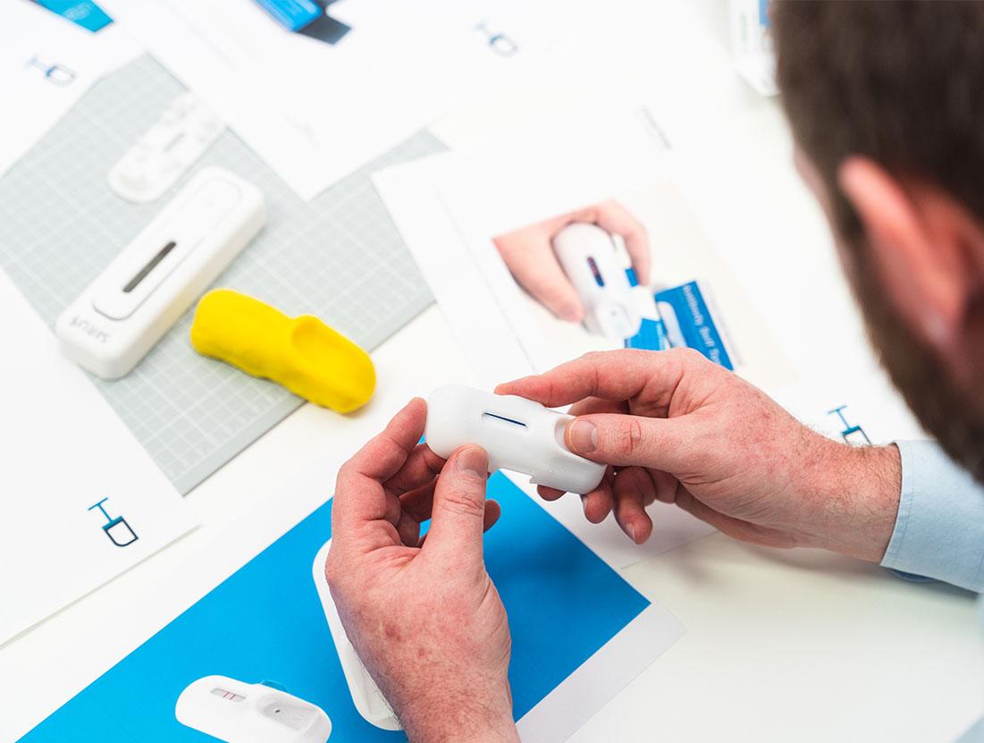 Design engineer reviewing 3D prints of an antibody blood sampling medical device