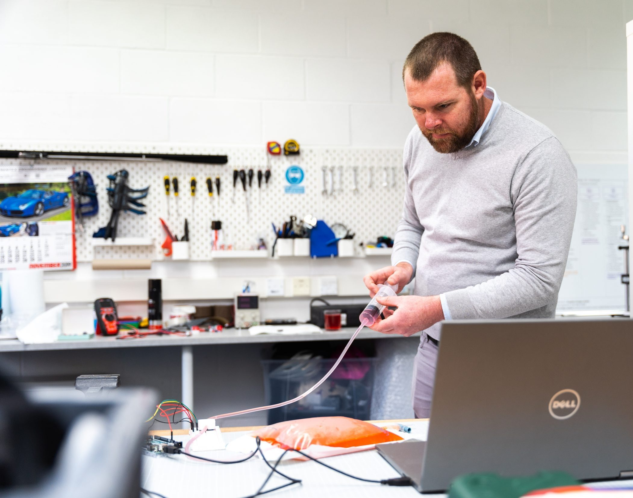 A medical device engineer pushing coloured liquid through a syringe whilst monitoring the outputs from a sensor