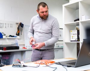 A Design Engineer testing a prototyped connected device concept with PCB board and medical device